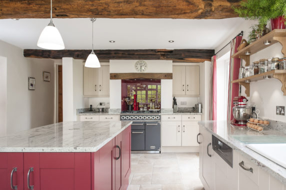 country cottage kitchen with red island and pendant lamps