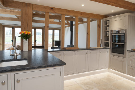 classic grey kitchen with dark worktops and beams