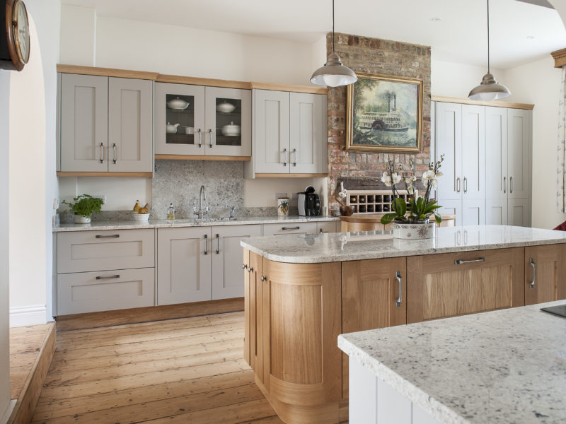grey kitchen with wood floor and island
