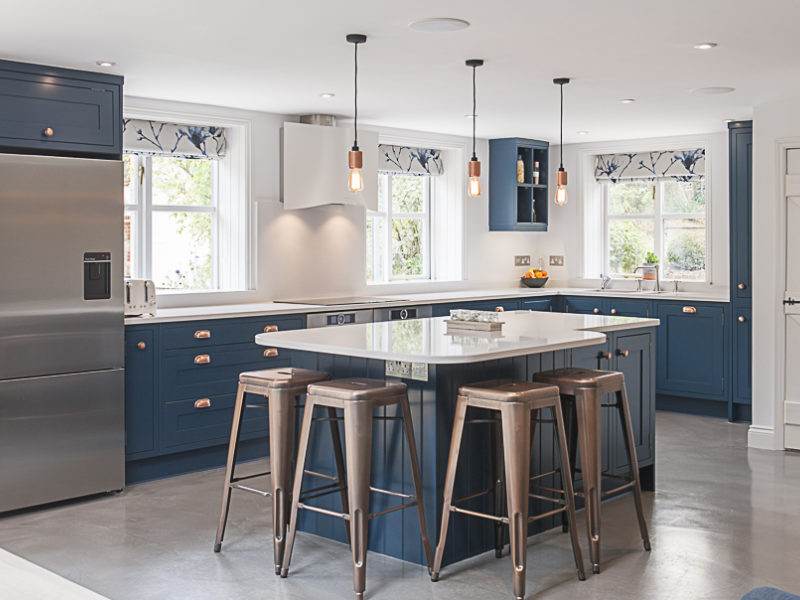blue kitchen with island and industrial barstools