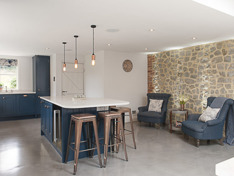 modern blue kitchen with island and living area