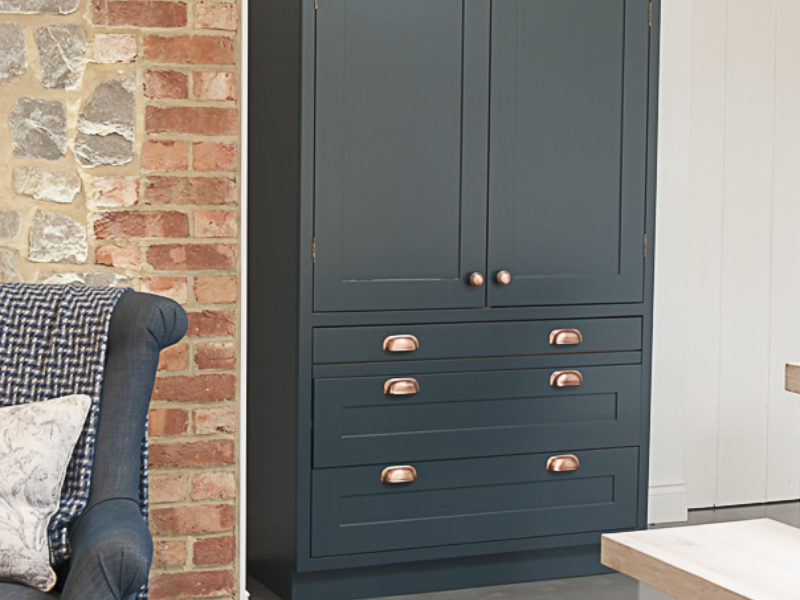 blue kitchen with freestanding storage and copper details
