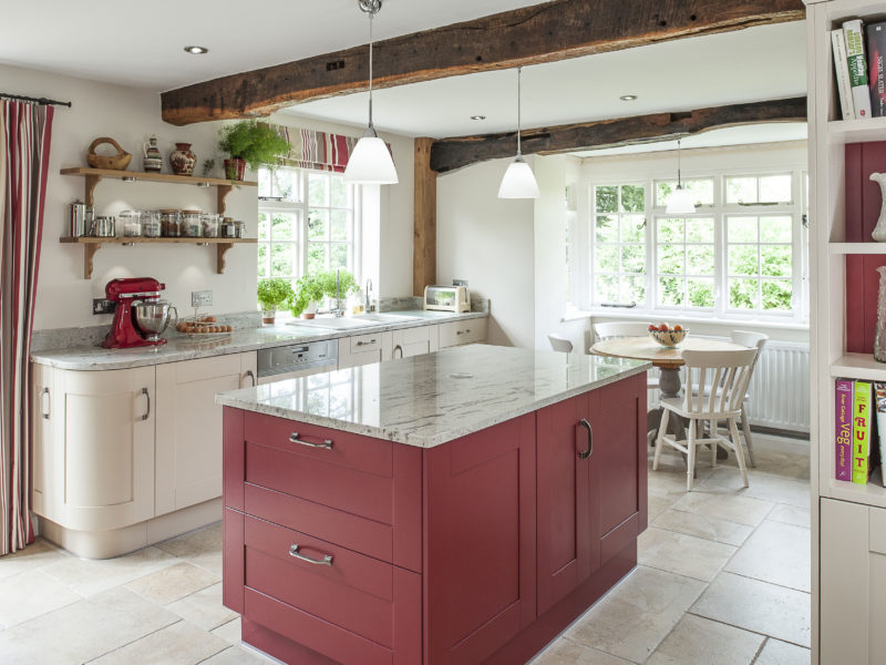 country cottage kitchen with red island and tiled floors