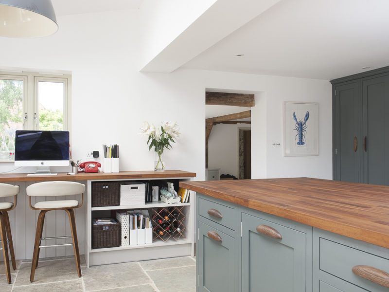 green kithen with wood worktops and stone floor