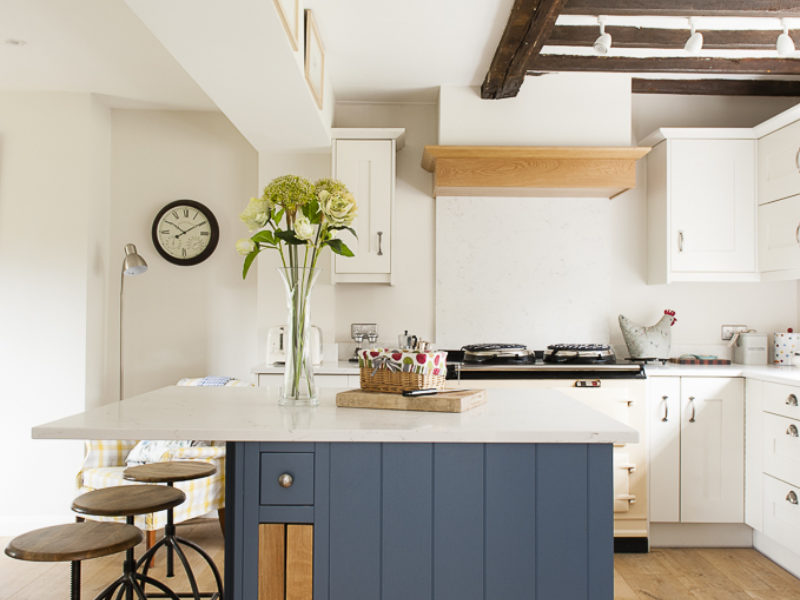 cottage kitchen with blue island and barstools