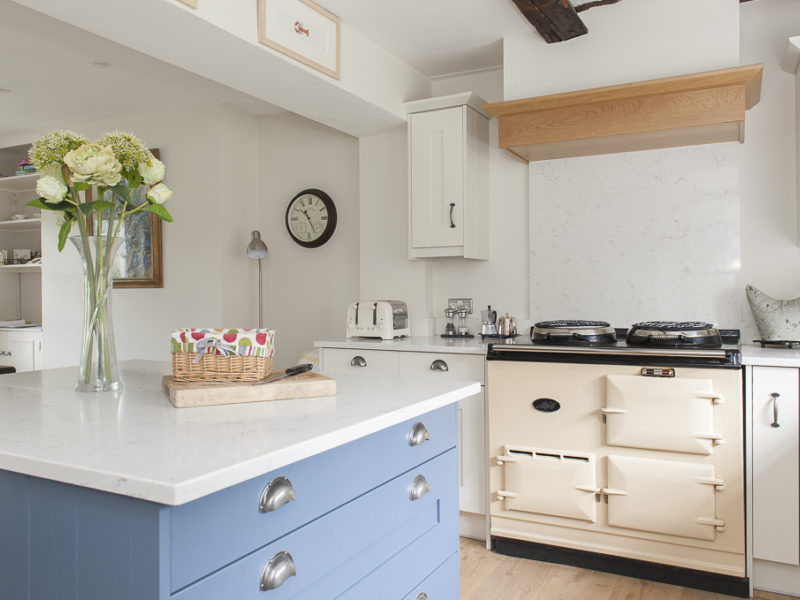 kitchen with blue island and cream range cooker