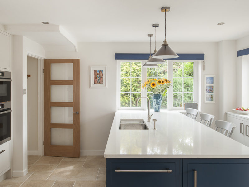 light airy kitchen with blue island and white worktops