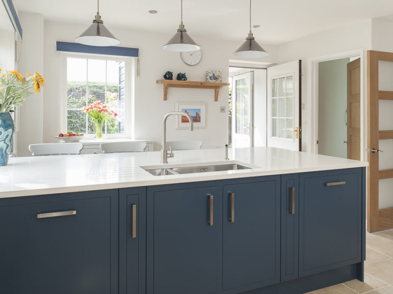 blue kitchen island with pendant lamps