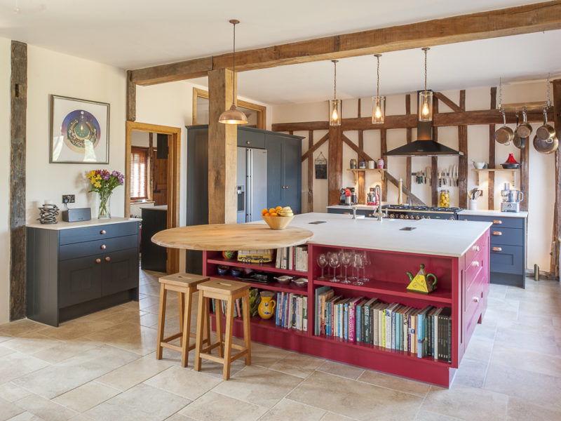 red kitchen island with pendant lights and breakfast bar