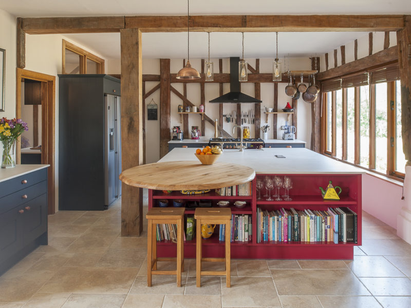 red kitchen island with beams and bar stools