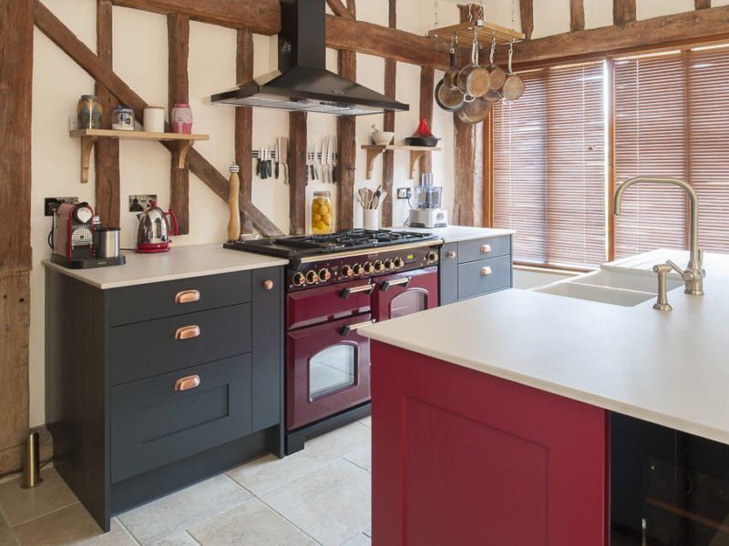 red kitchen with range cooker and beams