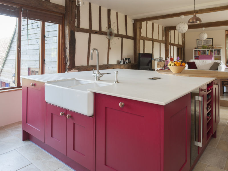 red kitchen island with belfast sink and beams