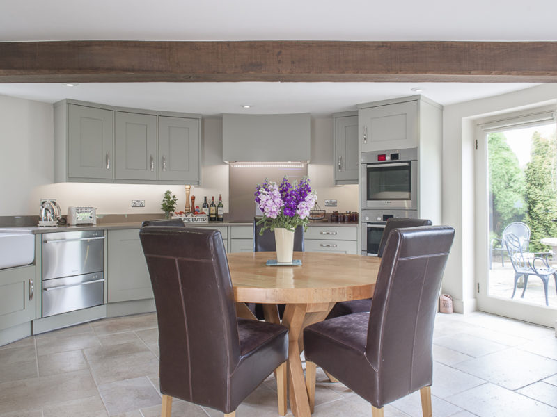 grey kitchen with beams and dining area