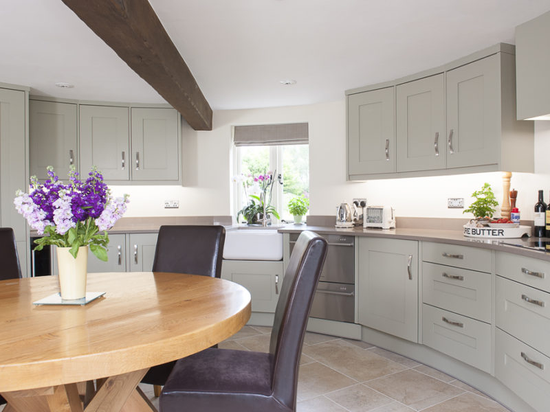 round grey kitchen with wood dining table