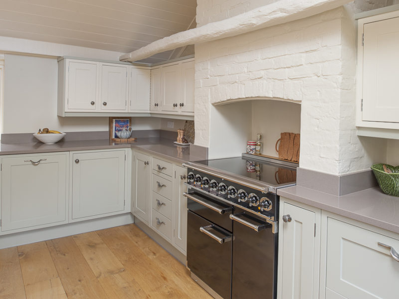 green kitchen with brick chimney and range cooker