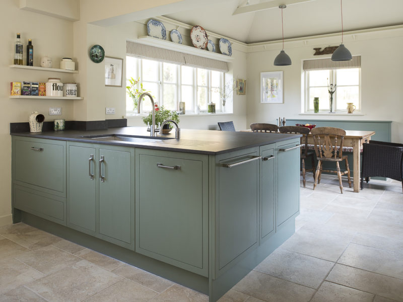 trendy green kitchen with island and pendant lamps