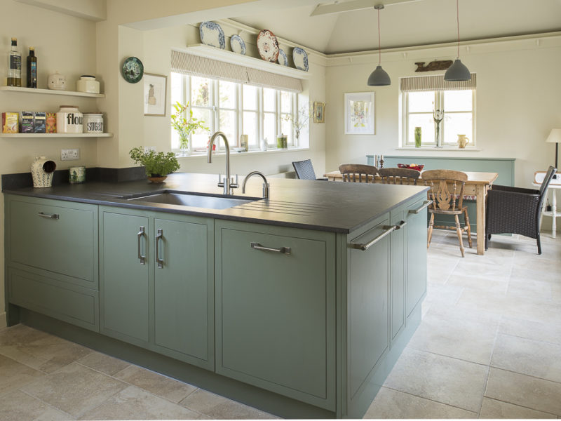 green kitchen island with tiled floor and pendant lights