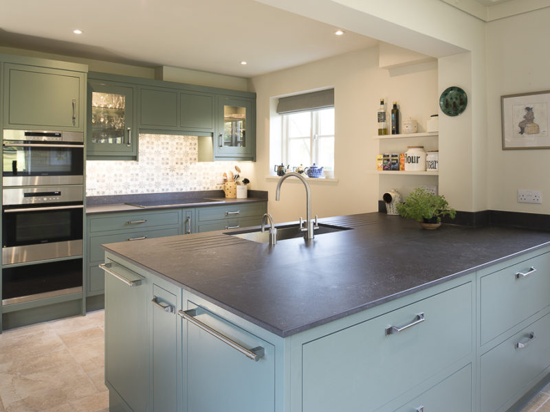 green kitchen with island and dark worktops
