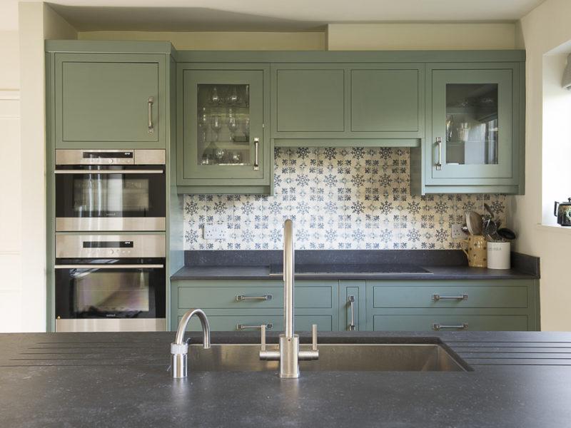 green kitchen with tiled splashback