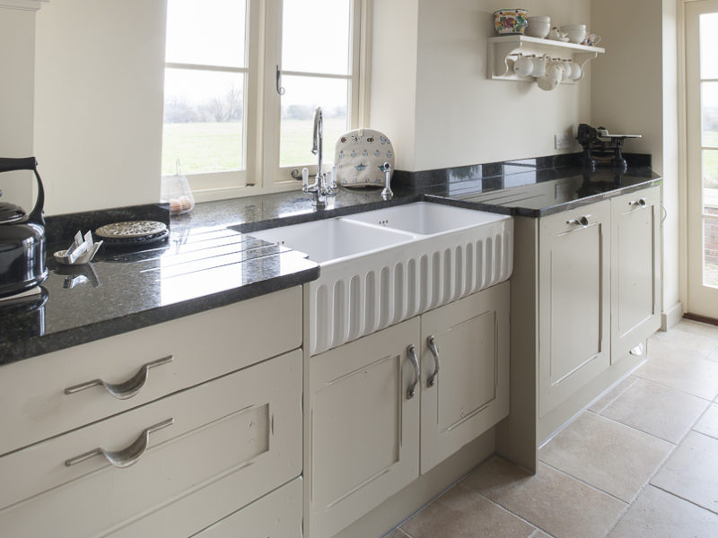 galley kitchen with black worktops and tiled floor